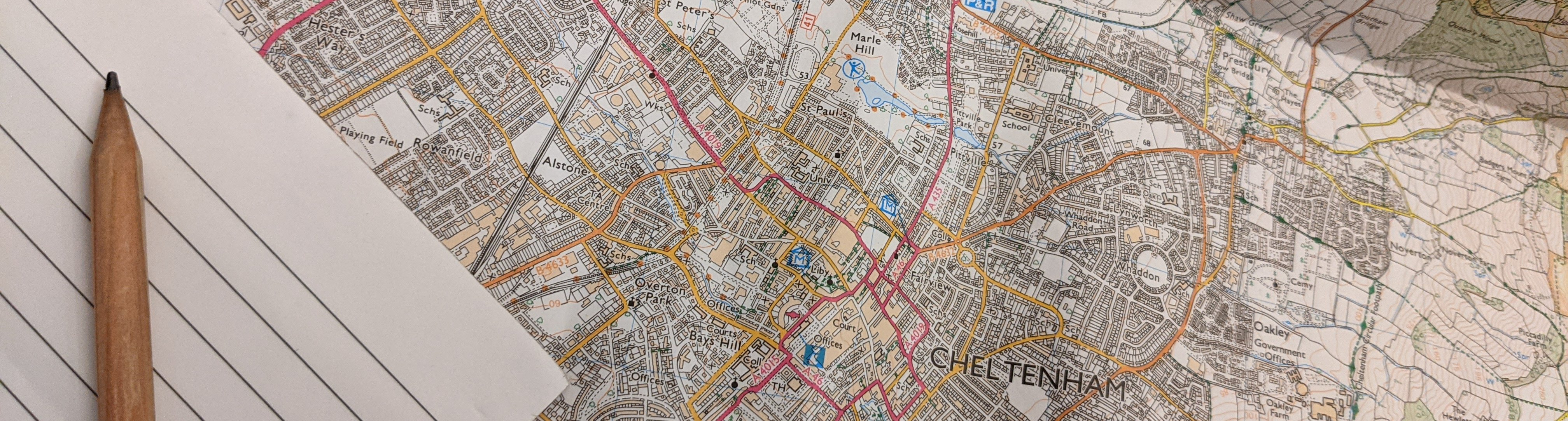 Map of Cheltenham with notepad and pencil